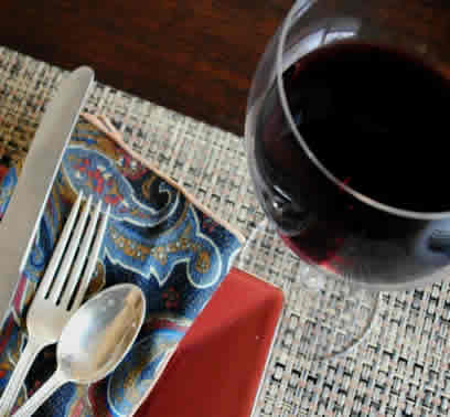 Dinner place setting with glass of red wine.