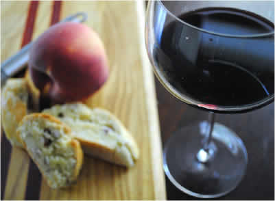 glass of red wine with peach and biscotti