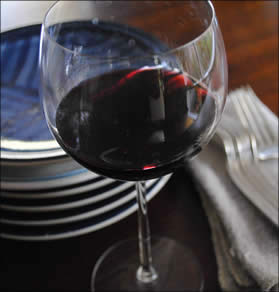 Glass of Dolcetto with plates and silverware