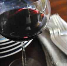 Glass of red wine with plates and silverware.