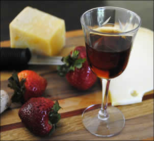 Glass of sweet Vinsanto wine with fruit and cheese