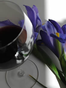 glass of red wine with iris in background