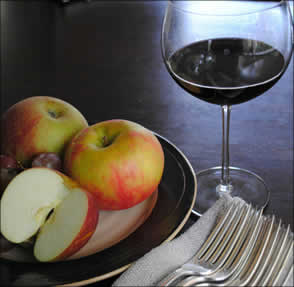Glass or red wine with plate of fruit
